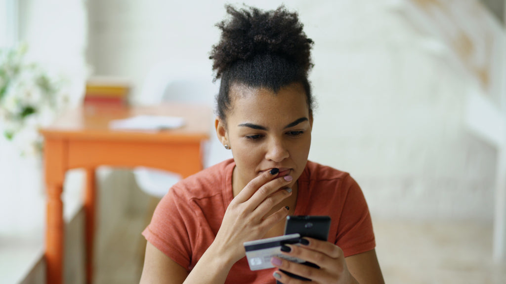 woman of color shopping on smartphone holding credit card