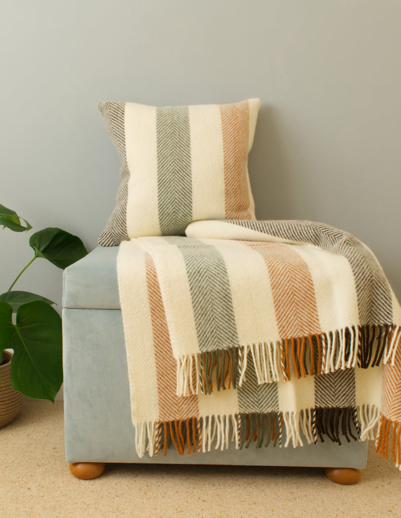 tweedmill woodland stripe wool cushion and throw on blanket box