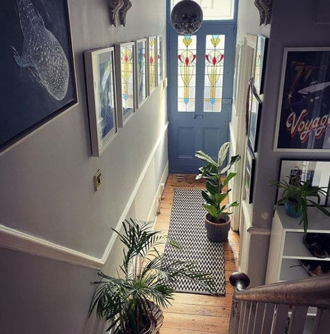 busy foyer with paintings on wall and hanging ceiling light