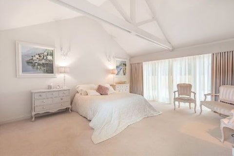 large white bedroom with high ceilings and double wall lights above bed