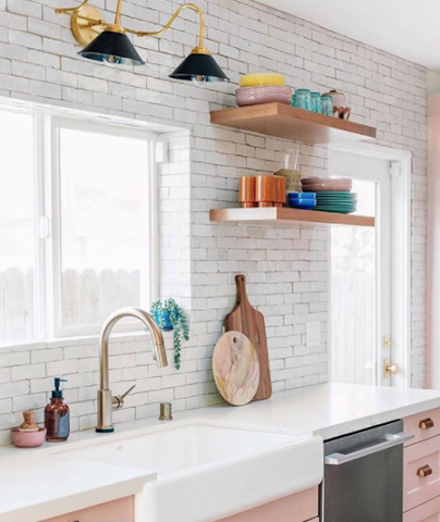 white and pink kitchen with gold wall lighting