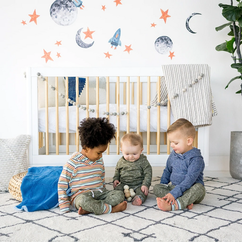 Three kids in a bedroom with spaceships wallpaper