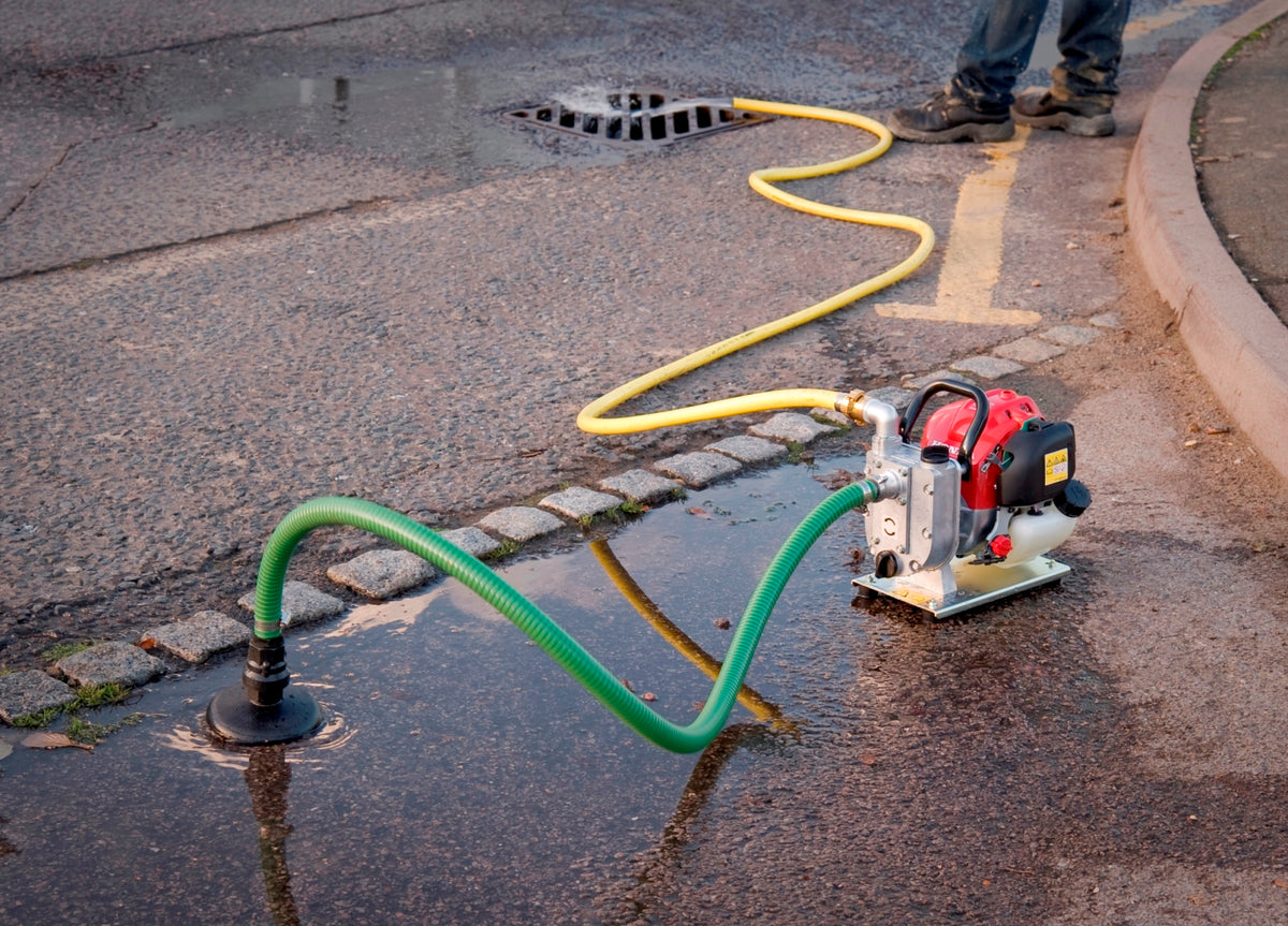 WX10 Honda Engine Driven Pump- location shot, pump shown removing water from road into drain, using hose attachments