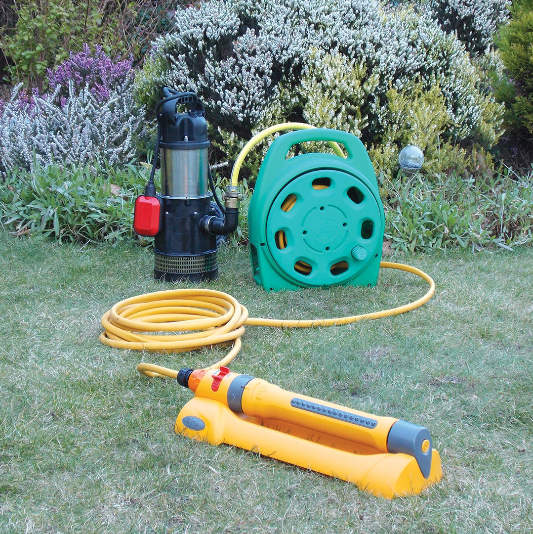MVH-10A Submersible Irrigation Pump- location shot, pump set up in garden ready to be used attached to hose and sprinkler