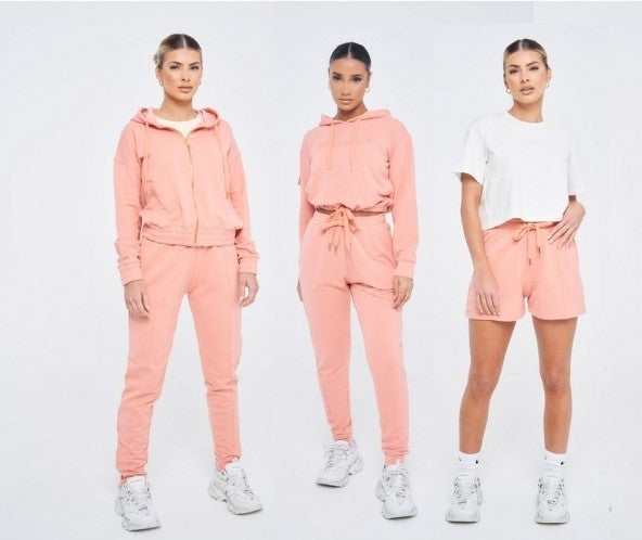 three models in the peach tracksuits. two wearing joggers and one wearing shorts