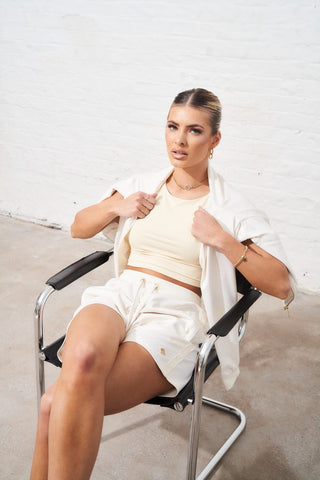 Model sat down, sporting our satin track suit shorts and jacket set accompanied by the tonal high neck crop top