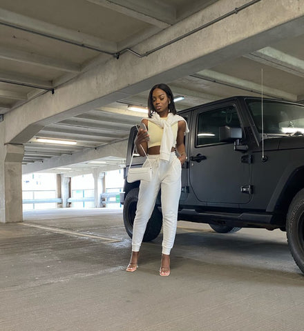 Influencer picture in a car park on her phone, wearing the signature joggers, heels and the tonal high neck crop top