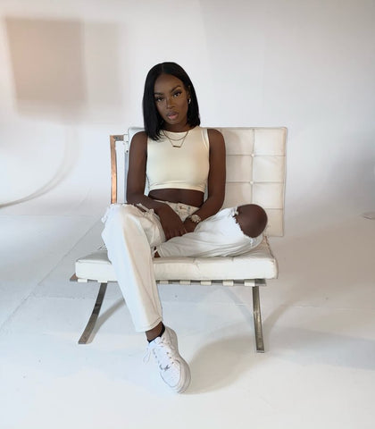 influencer image- sat down in the tonal high neck crop top in nude, accompanied by some white denim jeans and white trainers