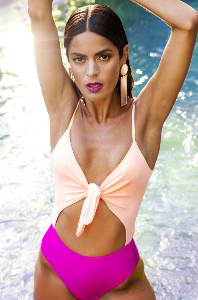 Dancing Leopard model in water wearing mix and match swimwear in pose with hands above her head