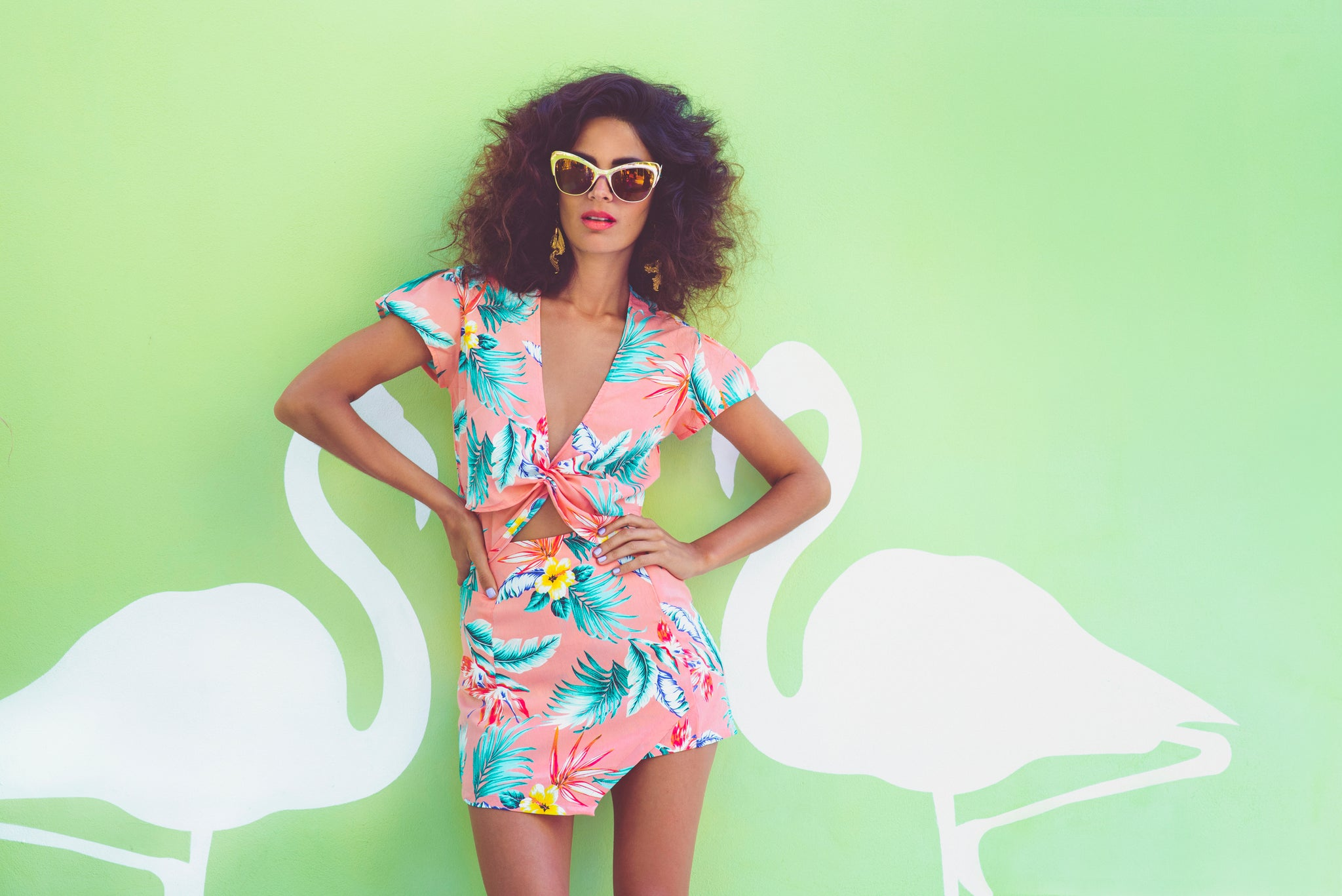 Sarah Qaiser wearing pink floral two piece in front of green flamingo background