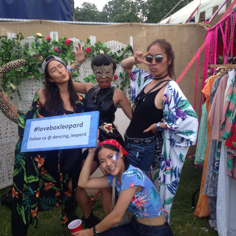 group of friends holding #loveboxleopard sign at Lovebox