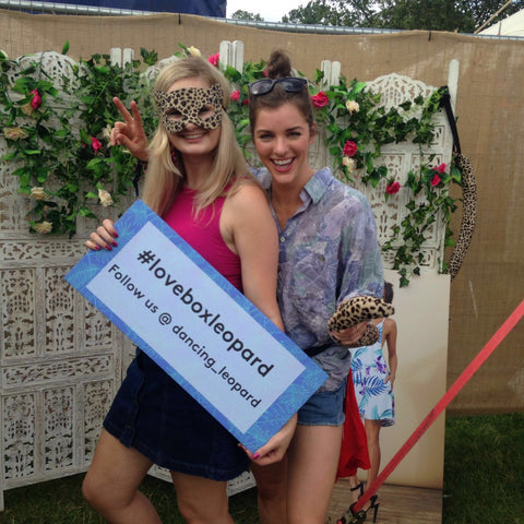 two girls holding #loveboxleopard sign at Lovebox