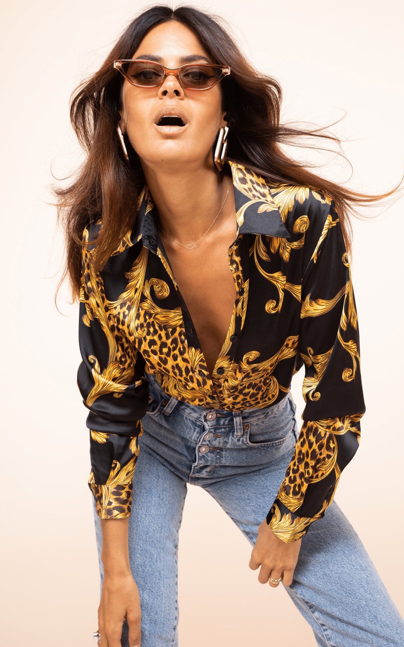Dancing Leopard model leans forward wearing sunglasses and Nevada Shirt in baroque print