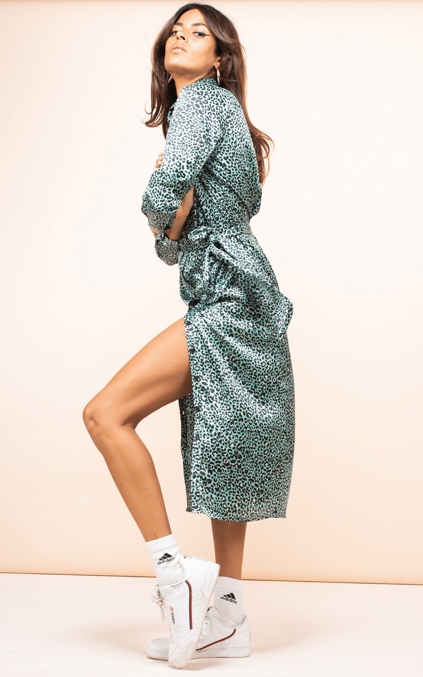Side-facing model wears Hadiba Midi Shirt Dress in mint leopard print with white trainers