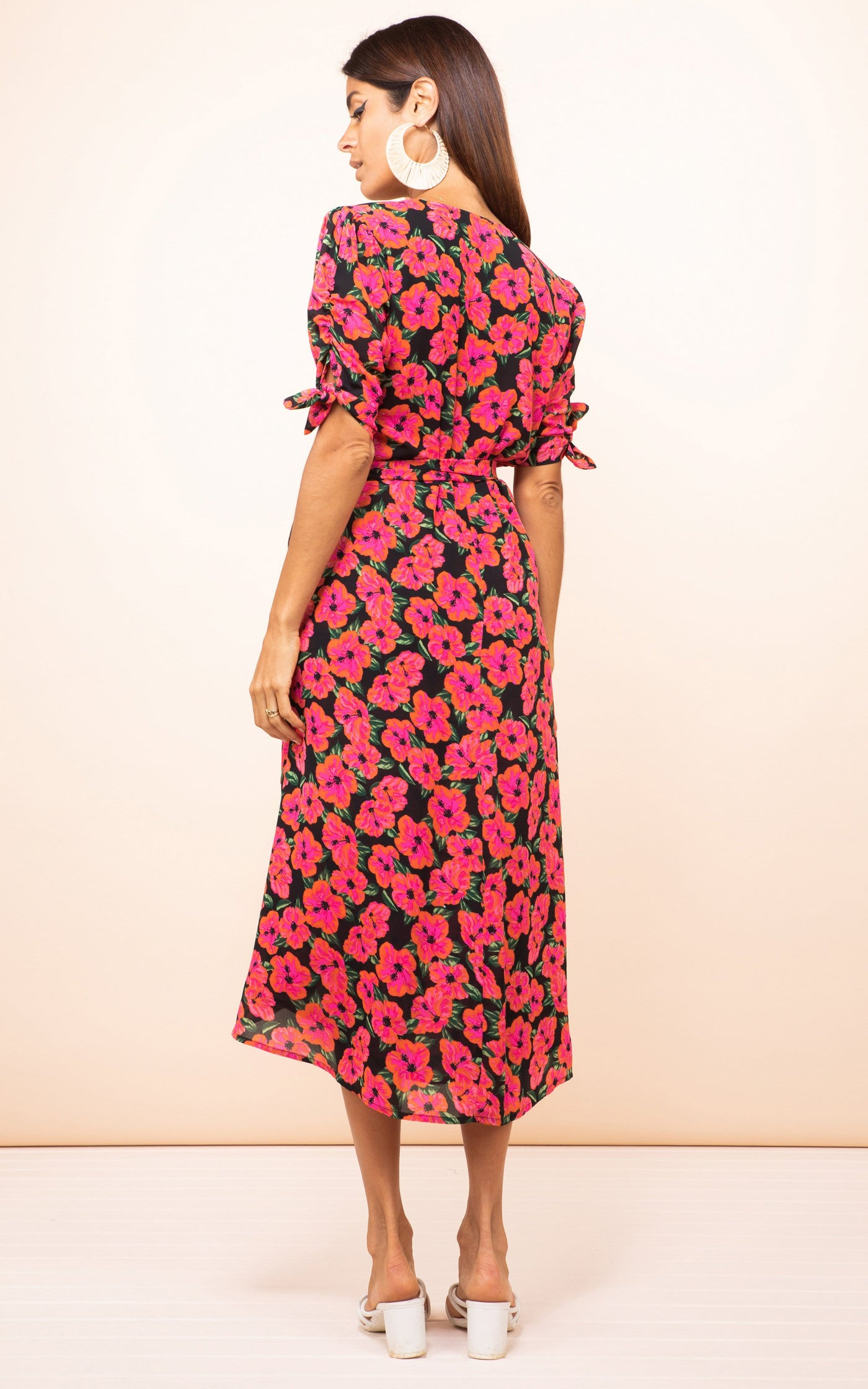 Dancing Leopard model faces backwards wearing Olivera Midi Dress in pink and black hibiscus print