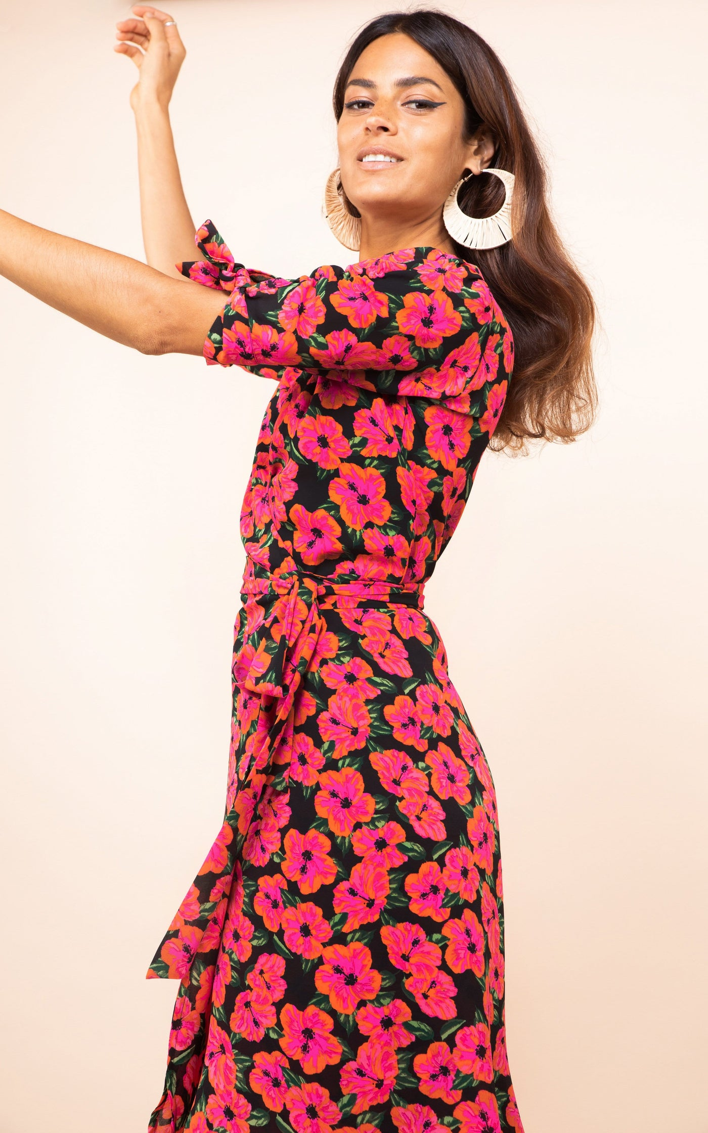 Dancing Leopard model faces sideways with arms up wearing Olivera Midi Dress in pink floral print