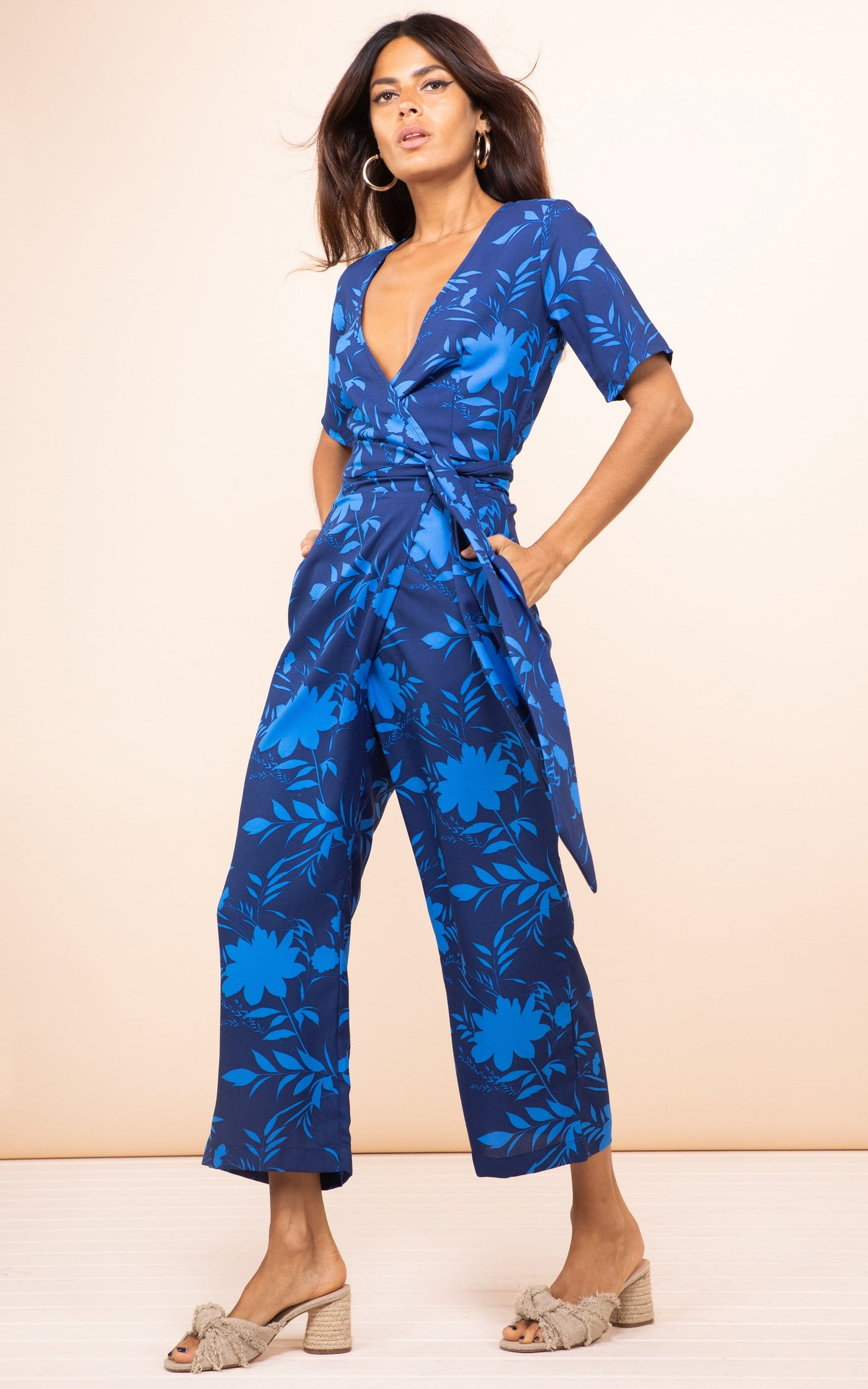 Front-facing model with hands in pockets wearing Dancing Leopard Atlantis Wrap Jumpsuit in blue floral print