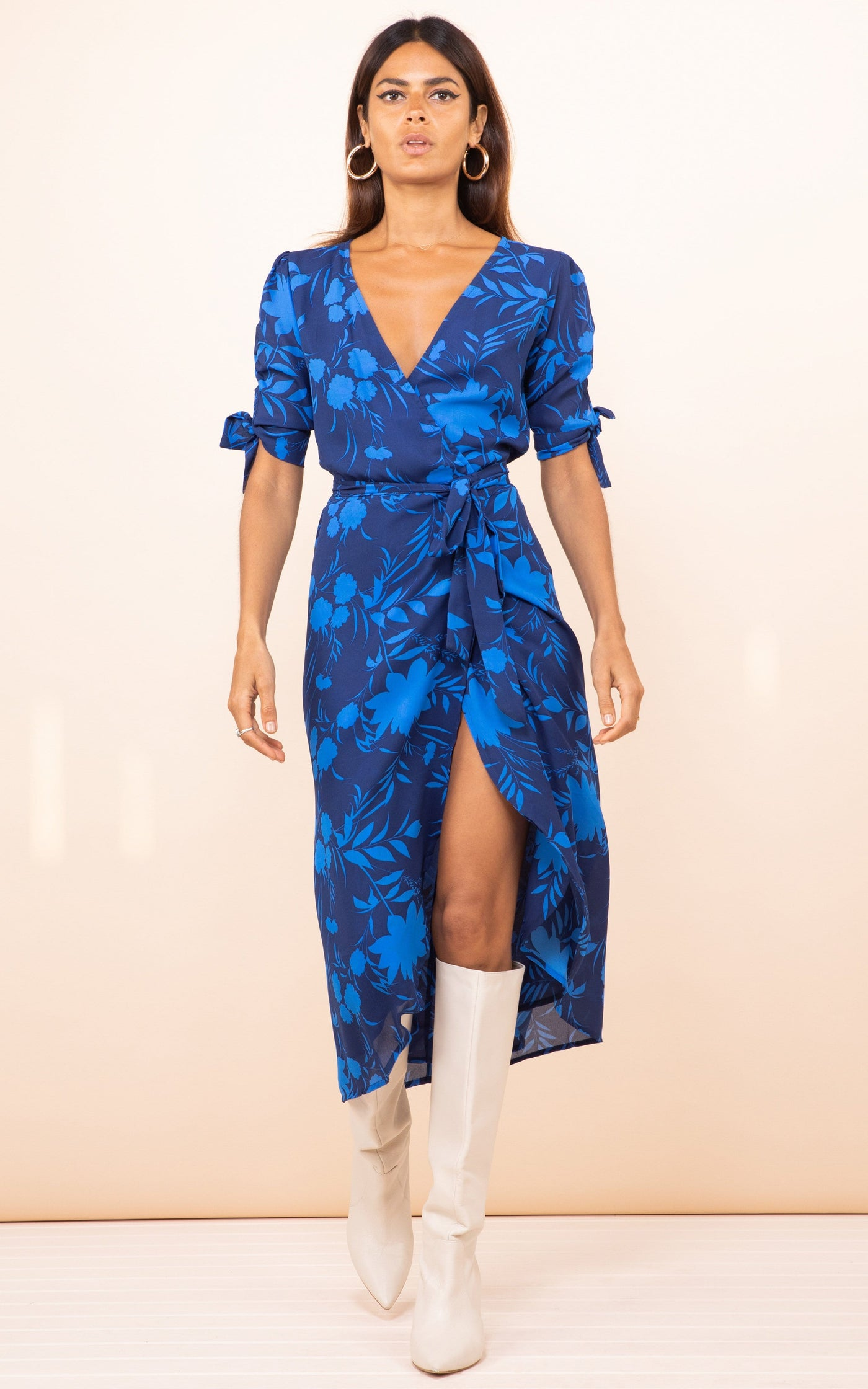 Model walks forward wearing Dancing Leopard Olivera Midi Dress in blue floral print with white boots