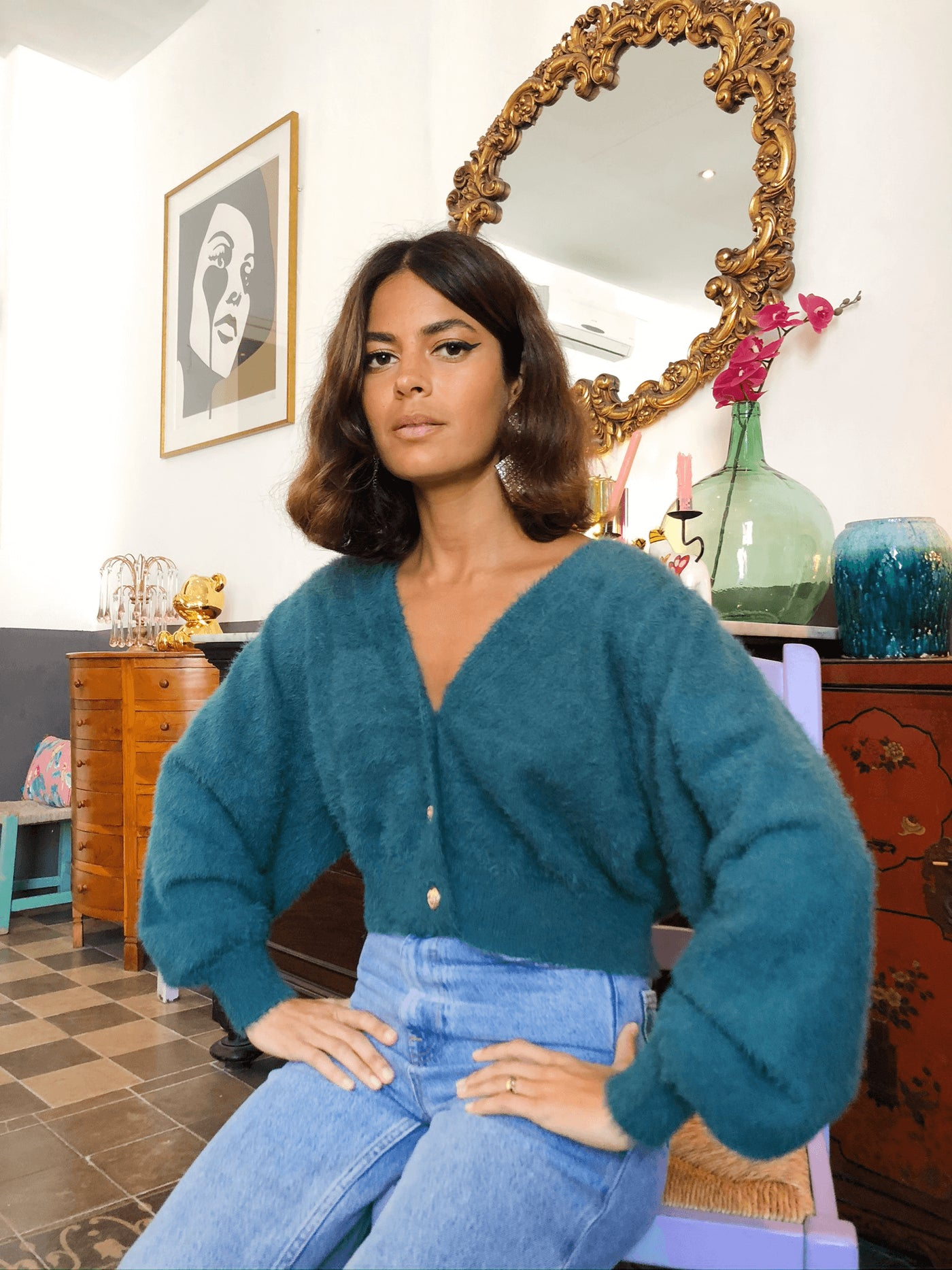 Dancing leopard model wears ariana cropped cardigan in forst green sitting down with jeans
