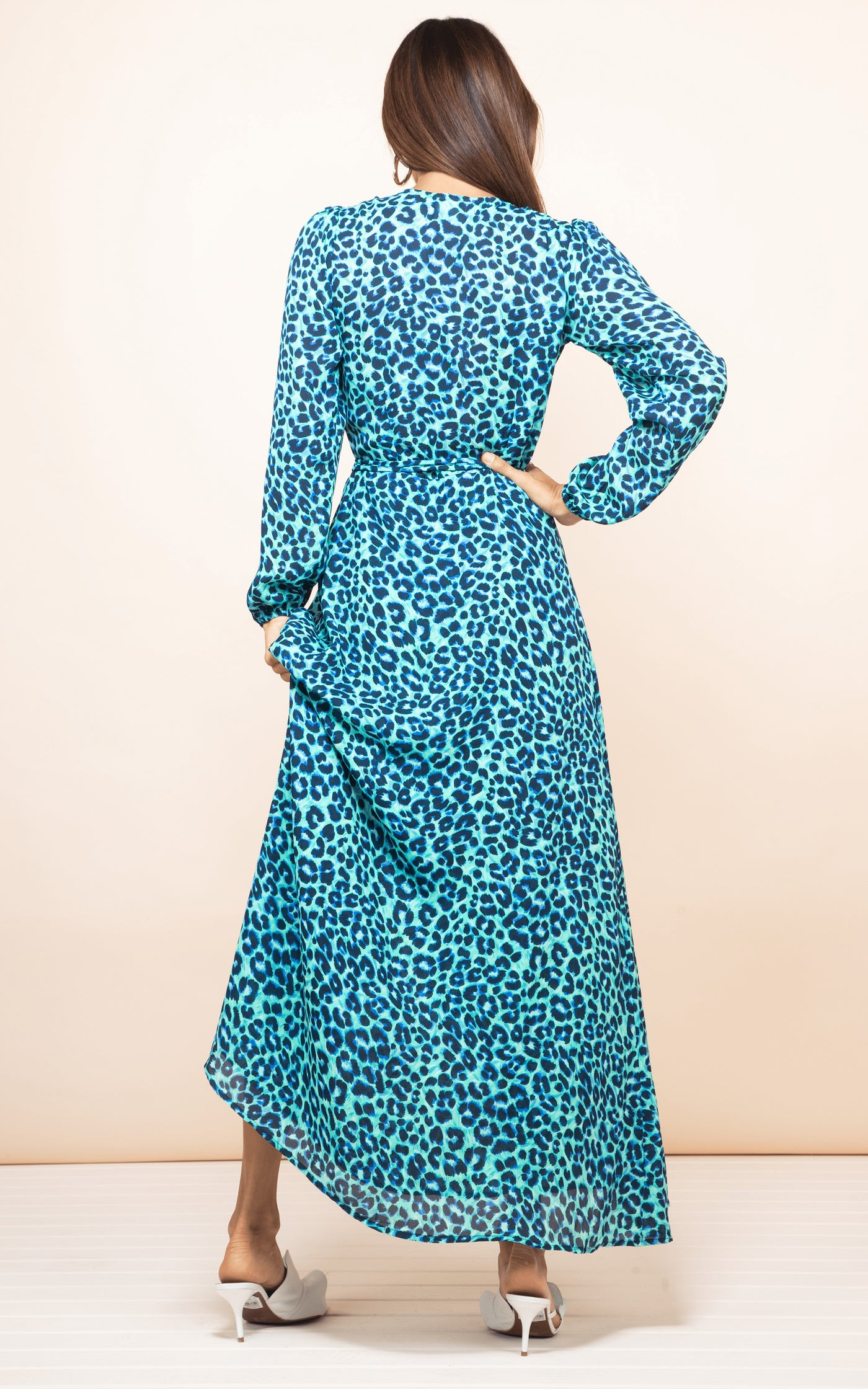 Backward-facing model with hand on hip wears Jagger Maxi Dress in turquoise leopard print