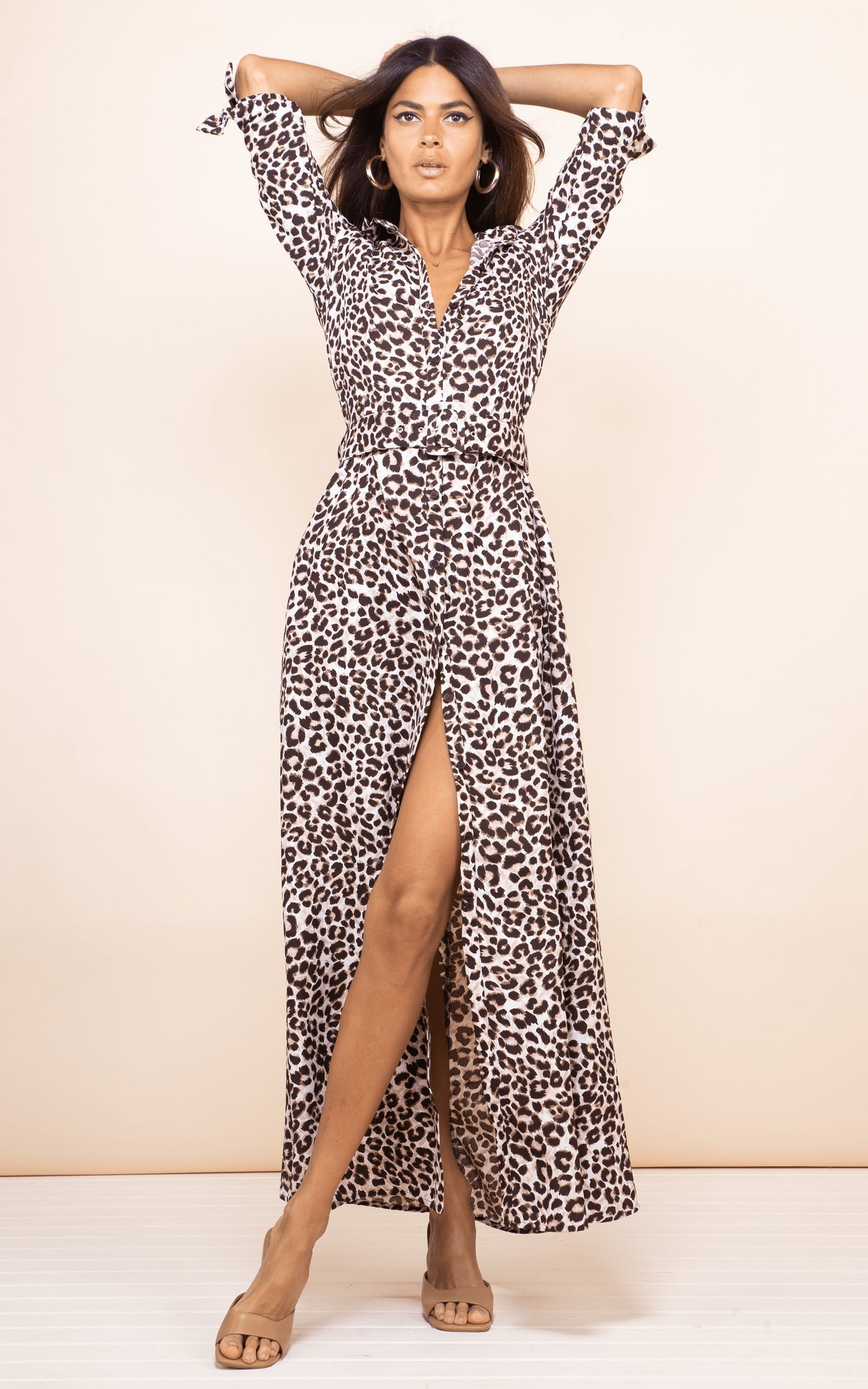 Front-facing brunette model with arms up wears Dove Dress in leopard print by Dancing Leopard