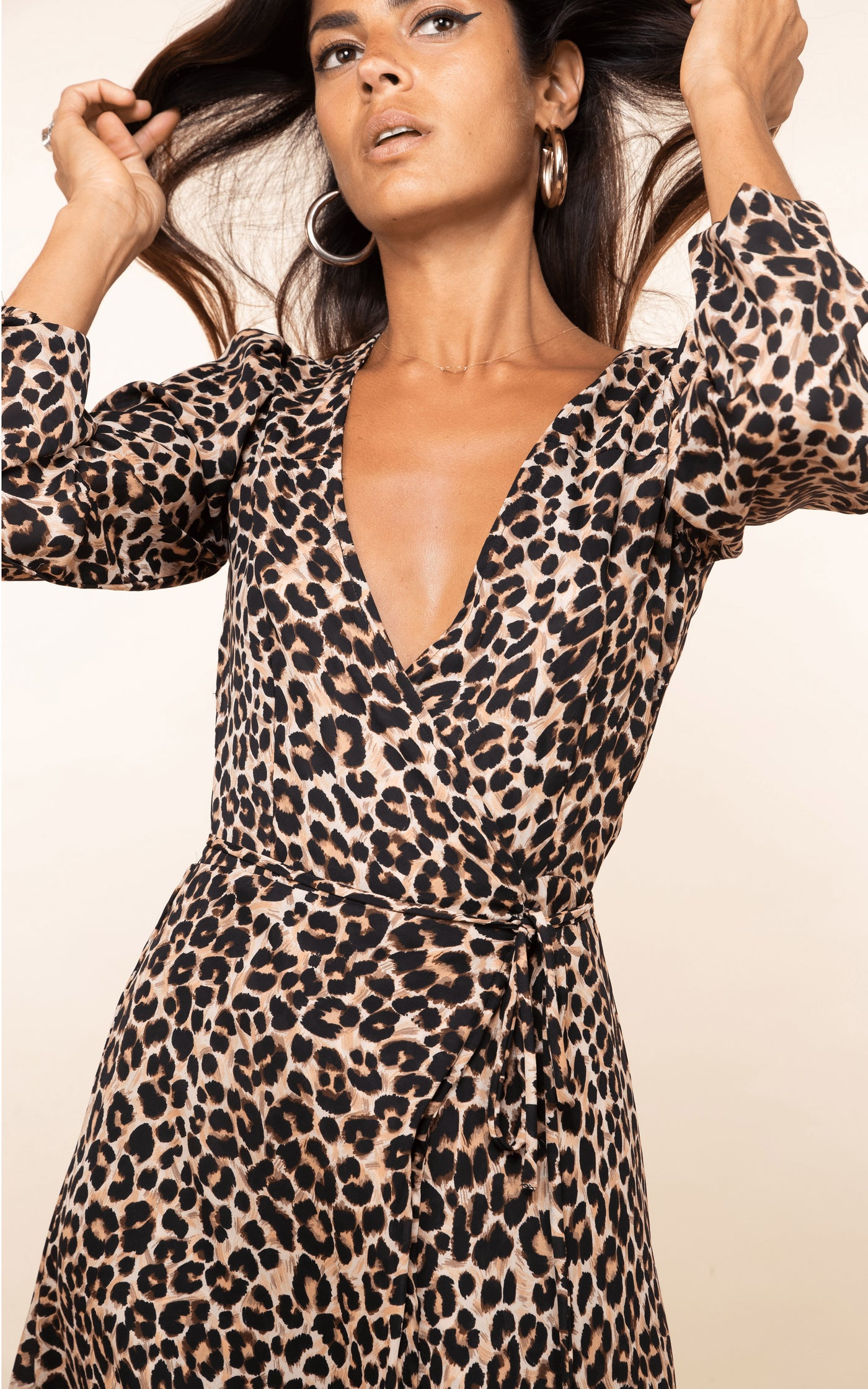 Dancing Leopard model flicks hair back wearing Jagger Maxi Dress in rich leopard print