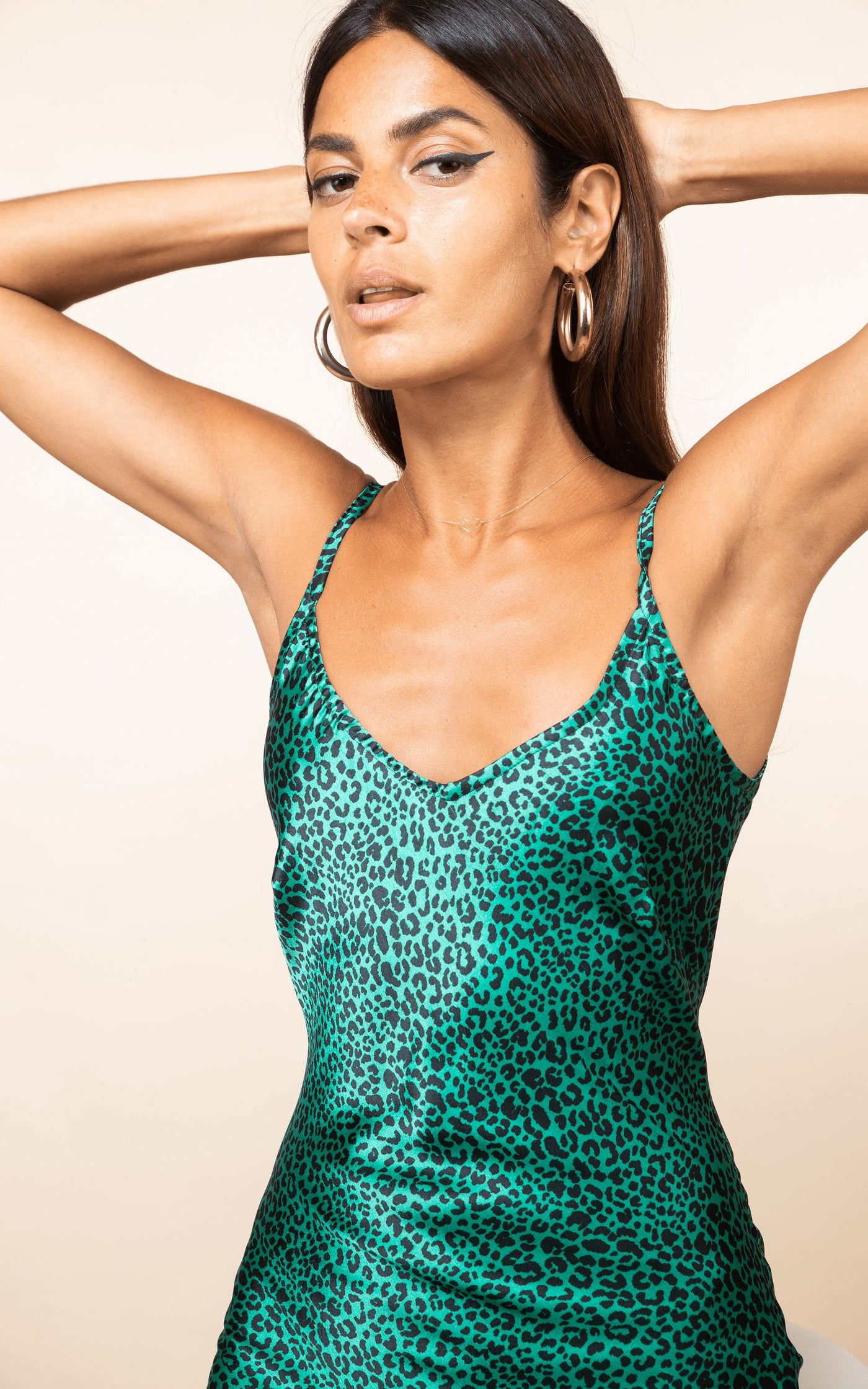 Dancing Leopard faces forward with arms behind head wearing Paloma Maxi Slip Dress in leopard print