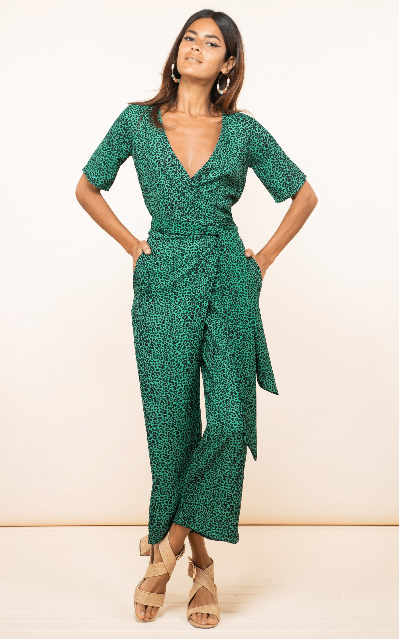 Dancing Leopard model faces forward wearing Atlantis Wrap Jumpsuit in green leopard print with hands in pockets