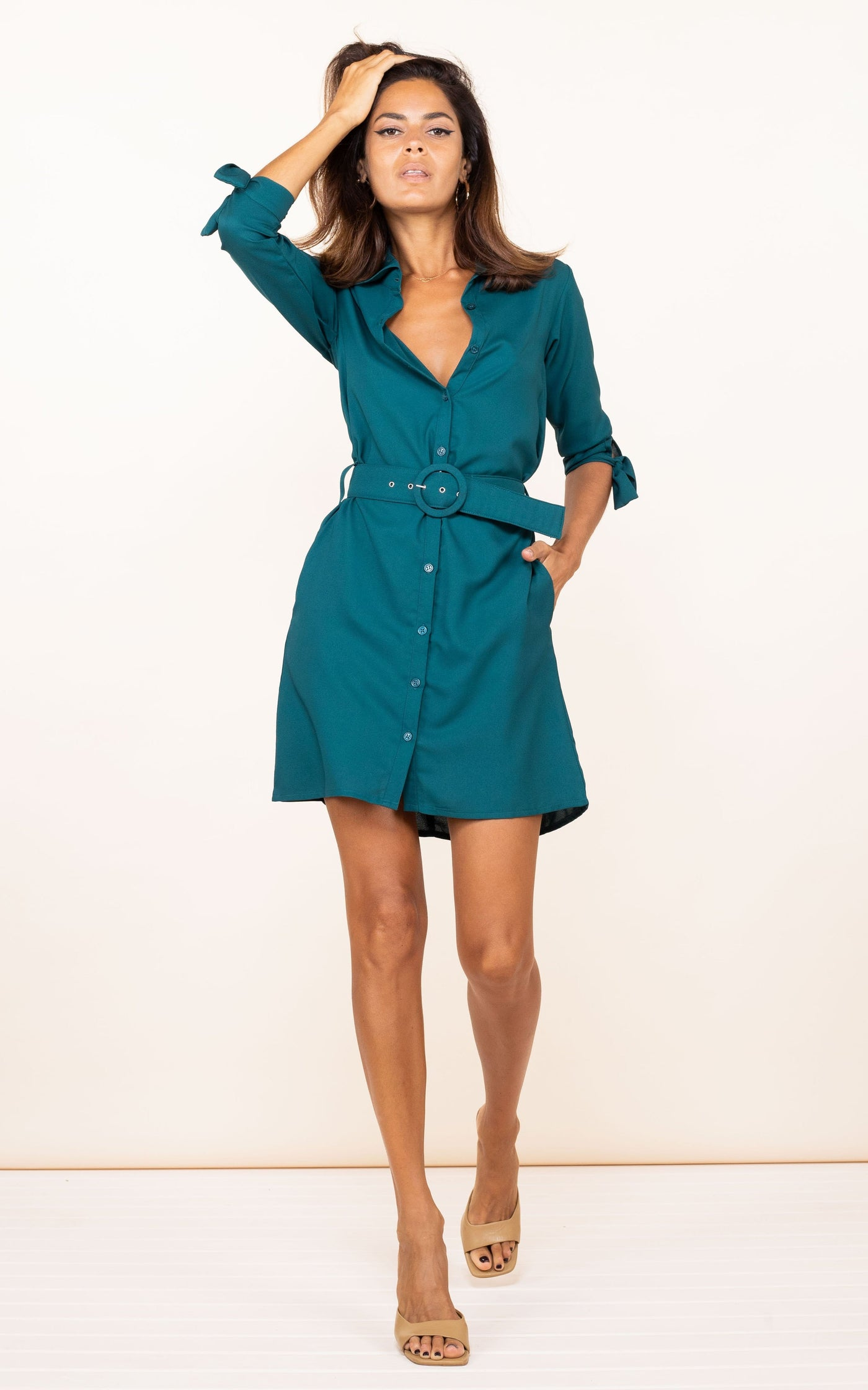 Dancing Leopard model faces forward with hand in hair wearing Jonah Mini Shirt Dress in pine green
