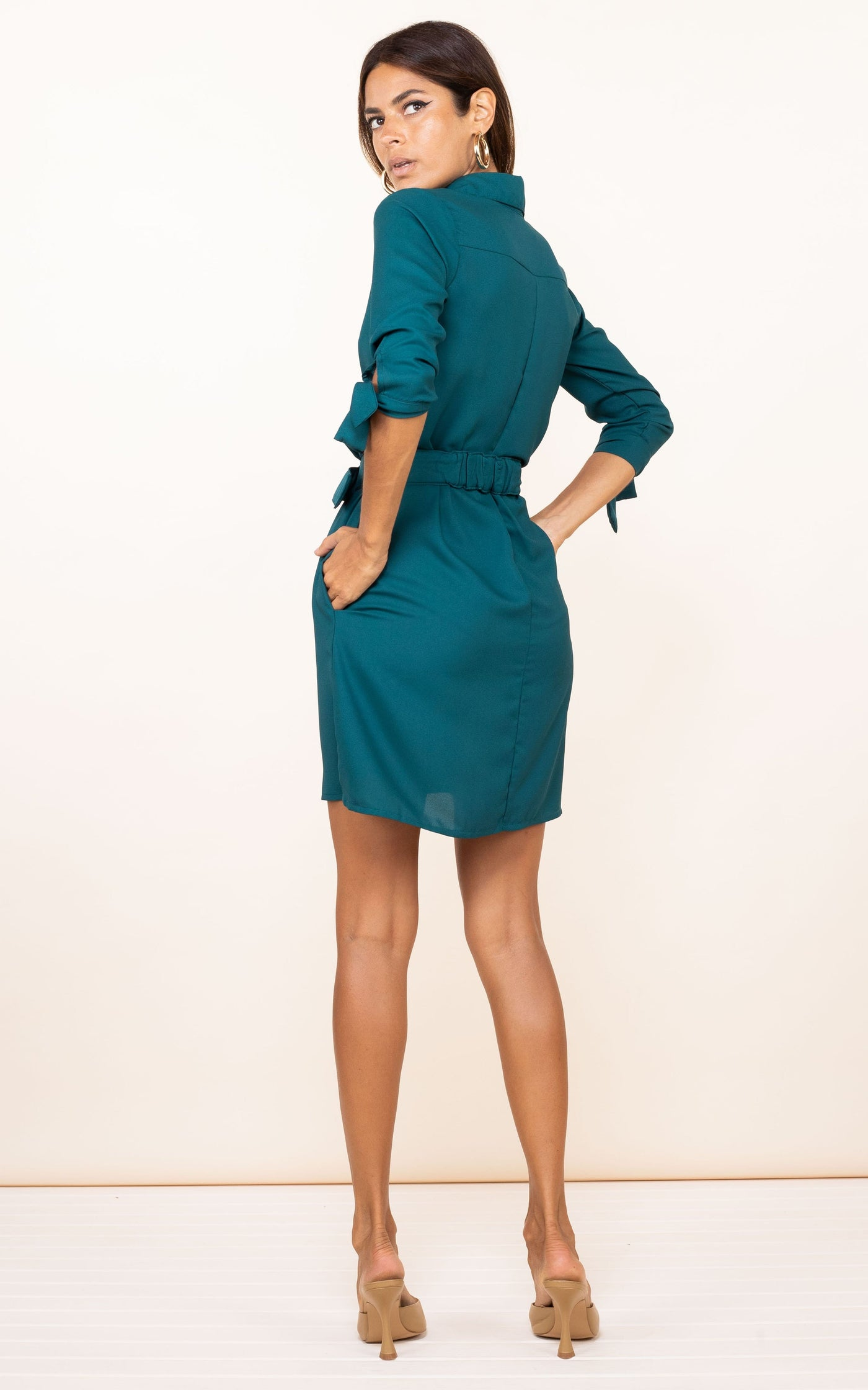 Dancing Leopard model faces backwards with hands in pockets wearing Jonah Dress in pine green