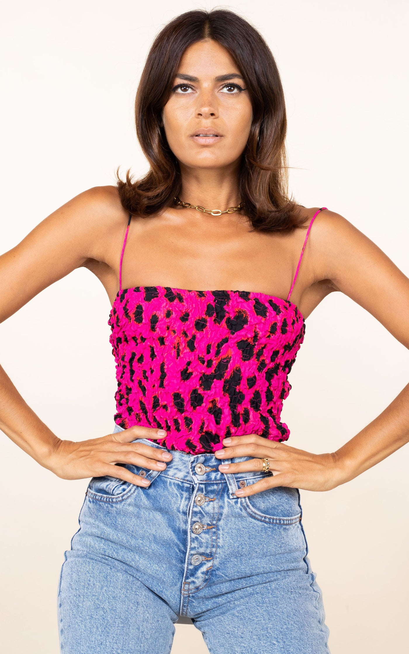 Dancing Leopard model faces forward with hands on hips wearing Storm Bodysuit in pink leopard print