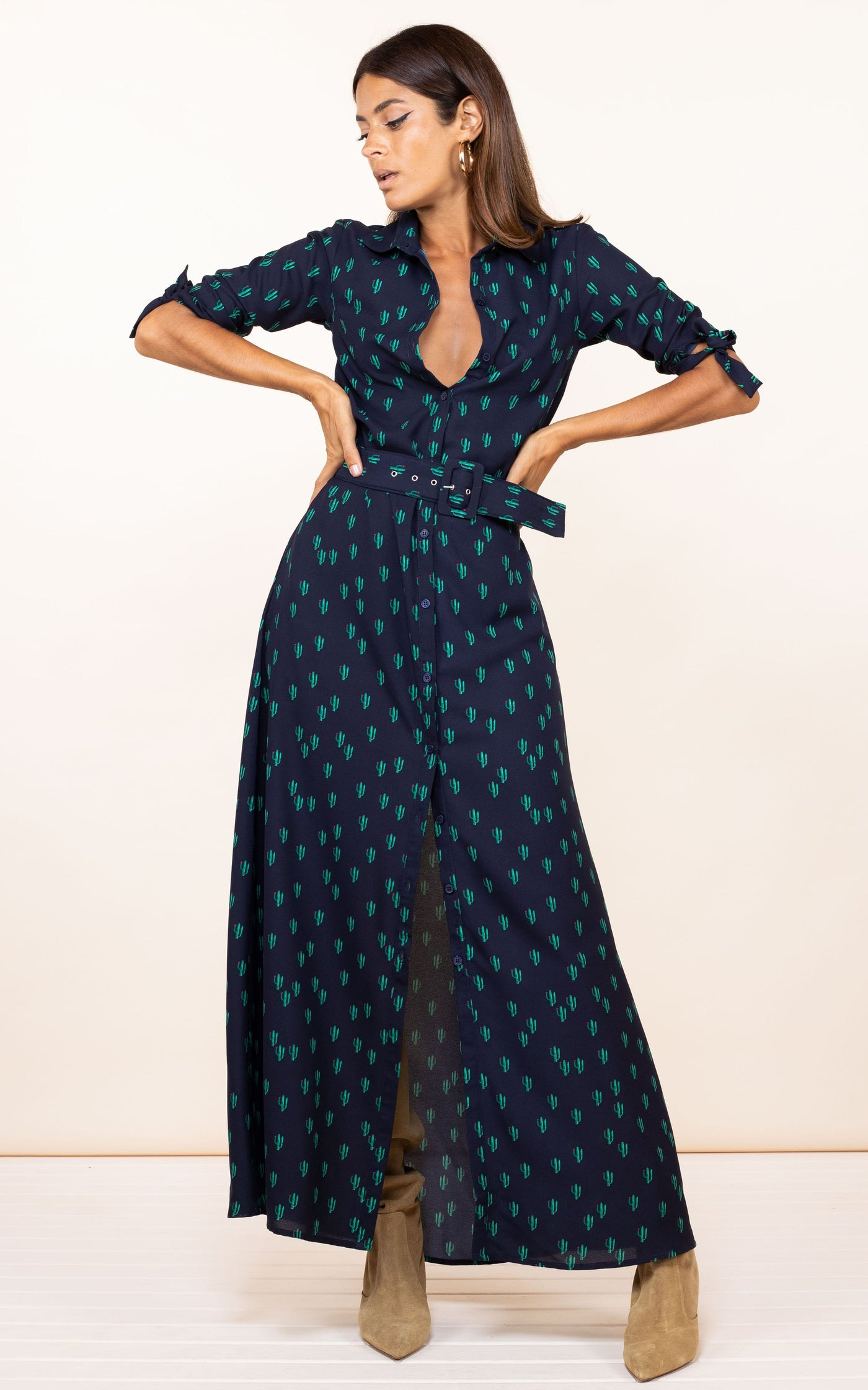 Dancing Leopard model faces forwards with hands on hips wearing Dove Dress in navy cactus print