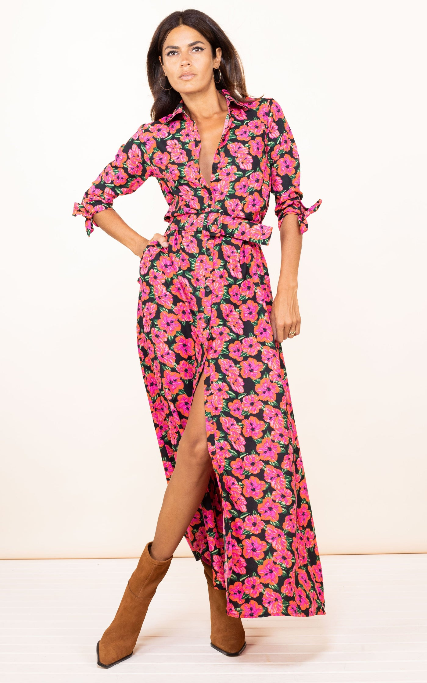 Dancing Leopard model faces forward with hand on hip wearing Dove Dress in pink on black hibiscus print