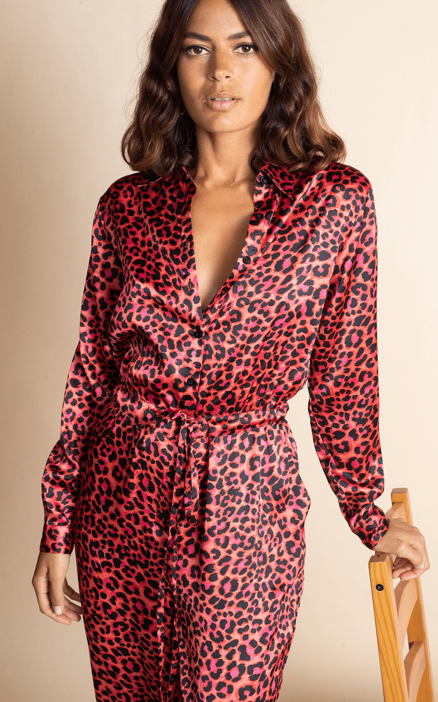 Dancing Leopard model facing forwards with hand on chair wearing Sami Jumpsuit in Ruby Red Leopard
