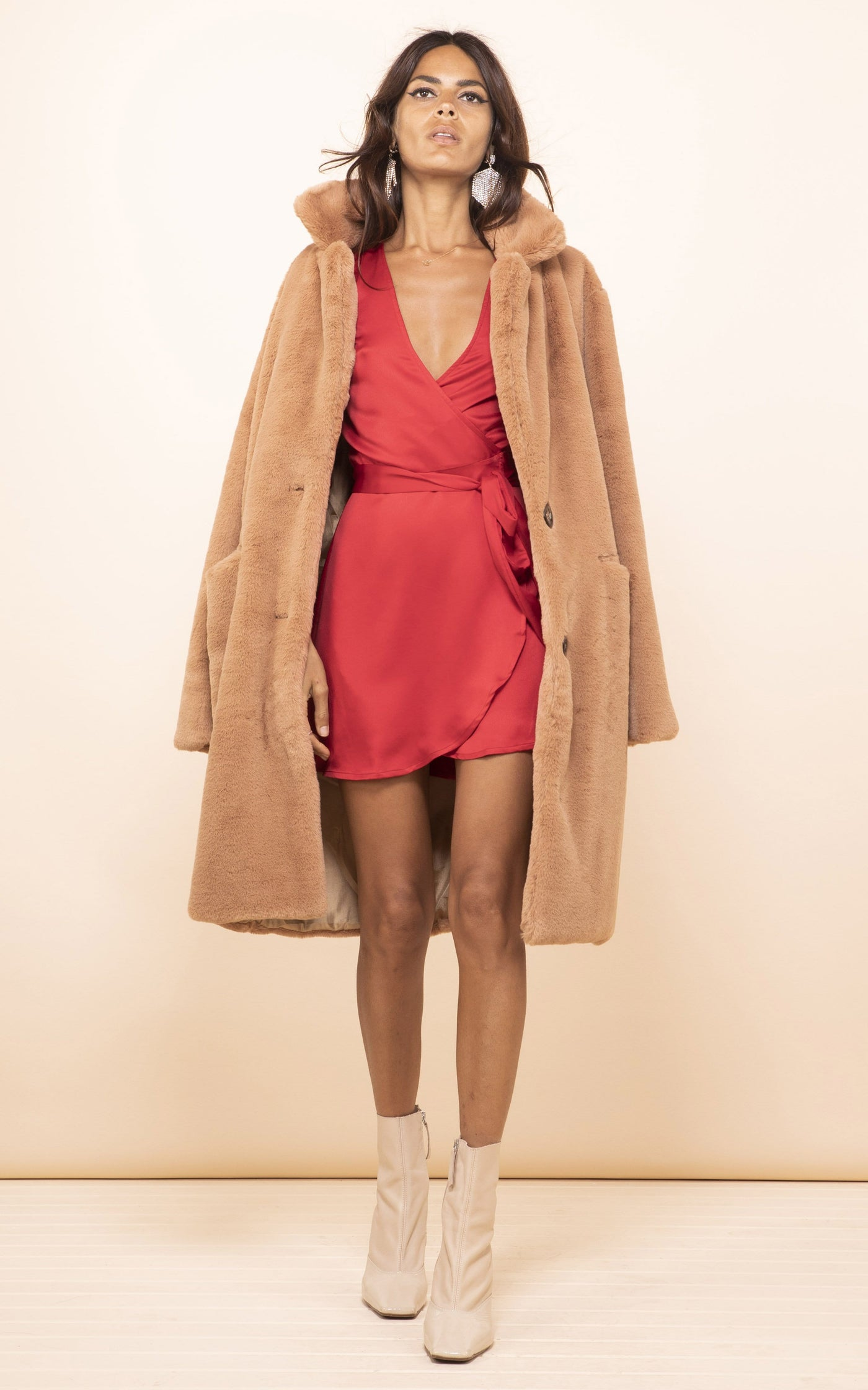 Dancing Leopard model walks forward wearing Marley Mini Dress in red with tan coat
