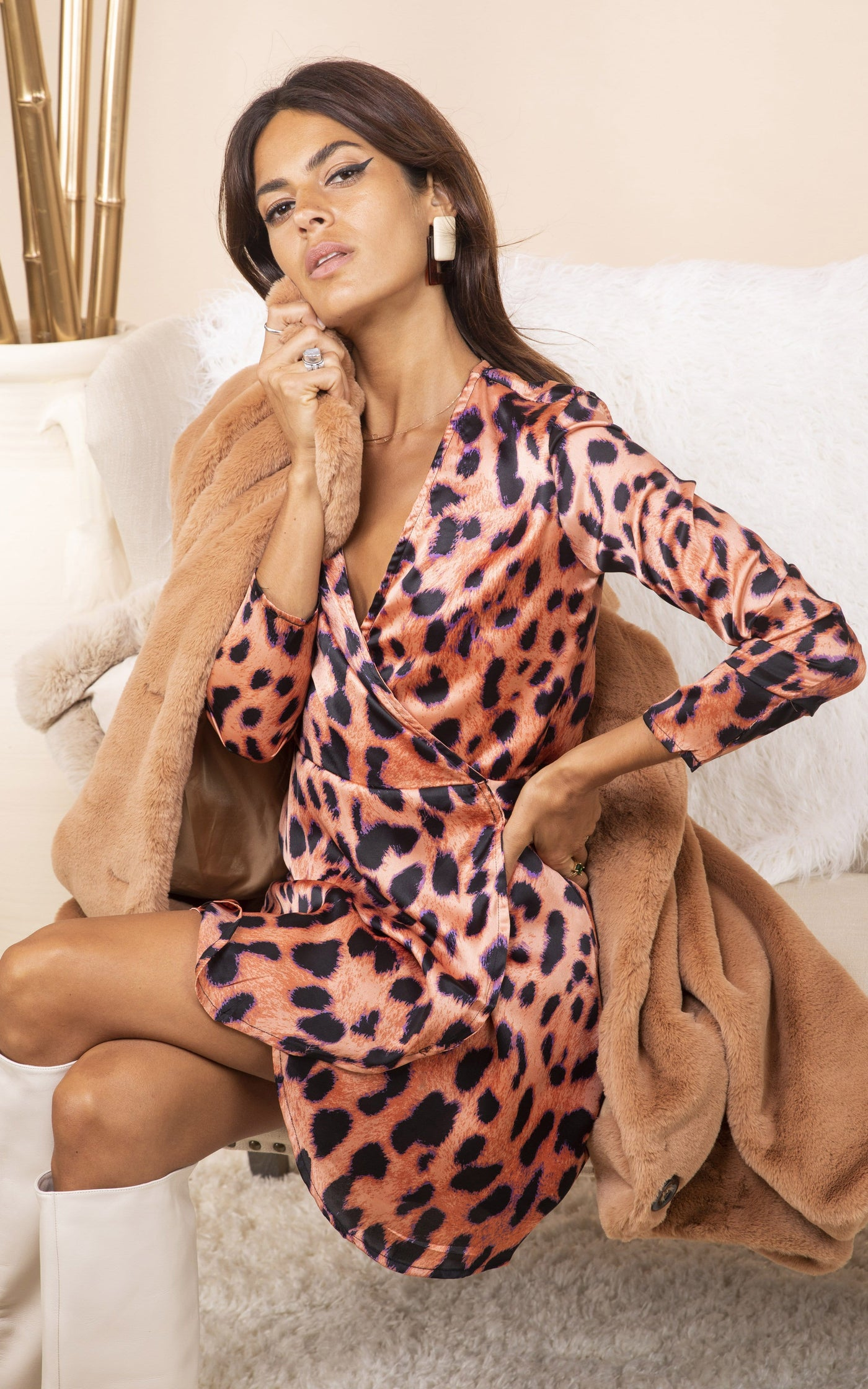 Dancing Leopard model sits down wearing tan coat and Marley Mini Dress in leopard print
