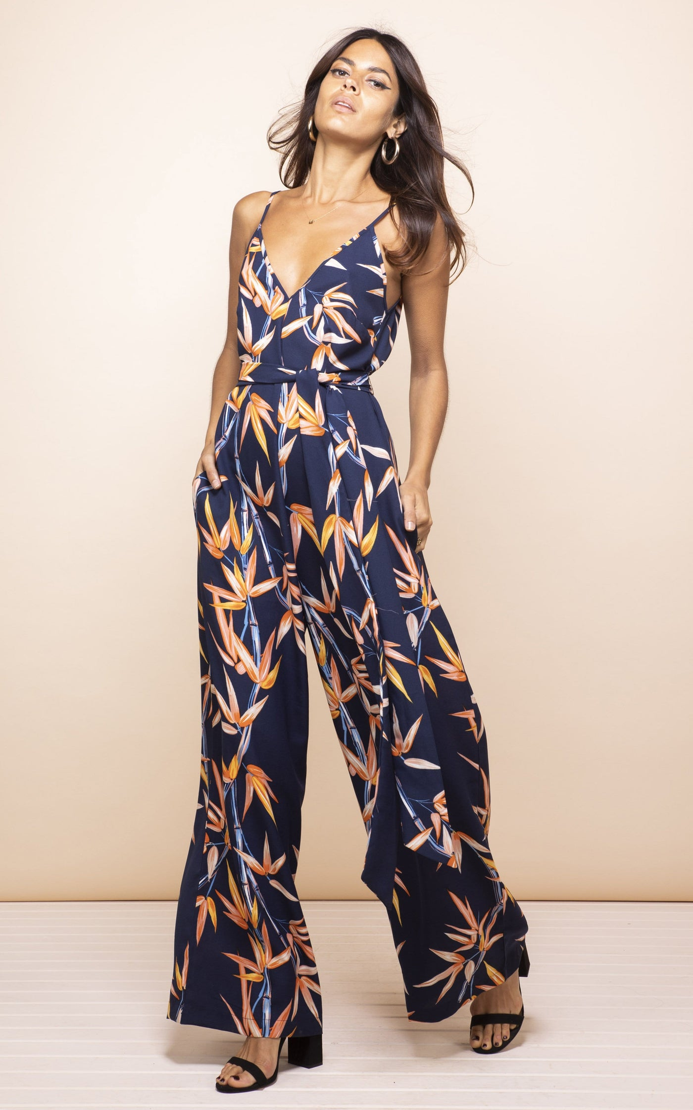 Front-facing model leans back wearing Gabriella Jumpsuit in navy and orange bamboo print
