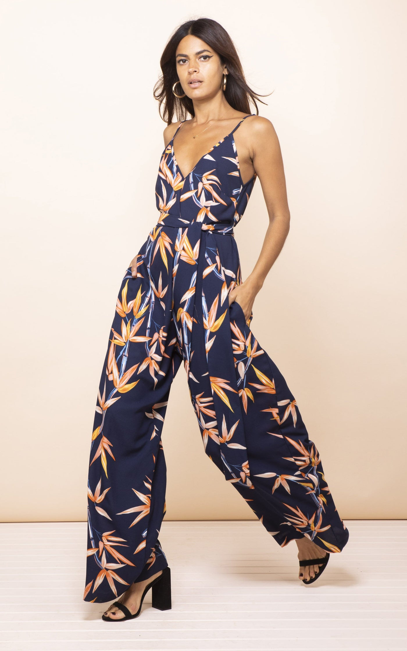 Dancing Leopard model walks to side with hand in pockets wearing Gabriella Jumpsuit in bamboo print