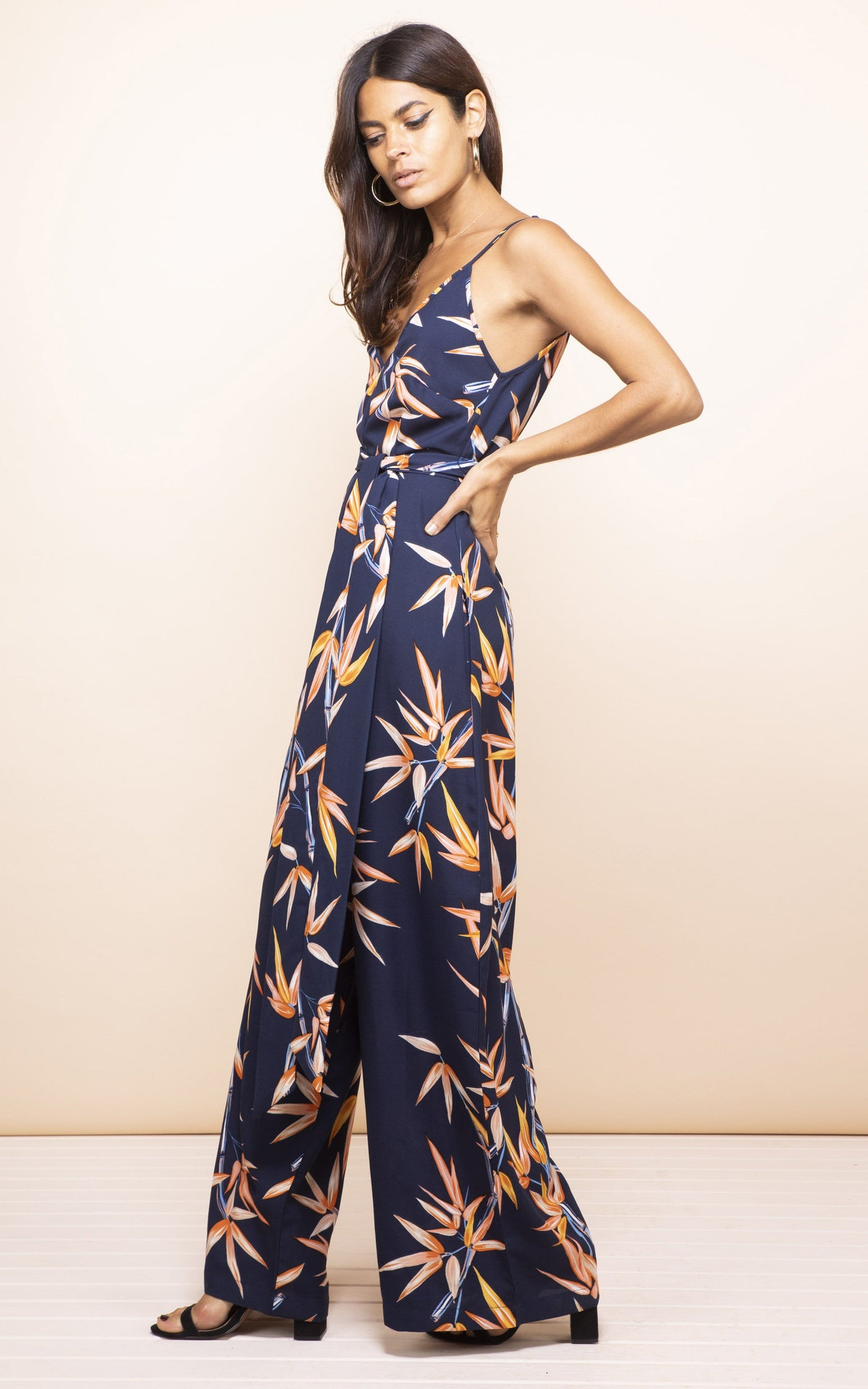 Side-facing model with hand on hip wears Gabriella Jumpsuit in navy and orange bamboo print