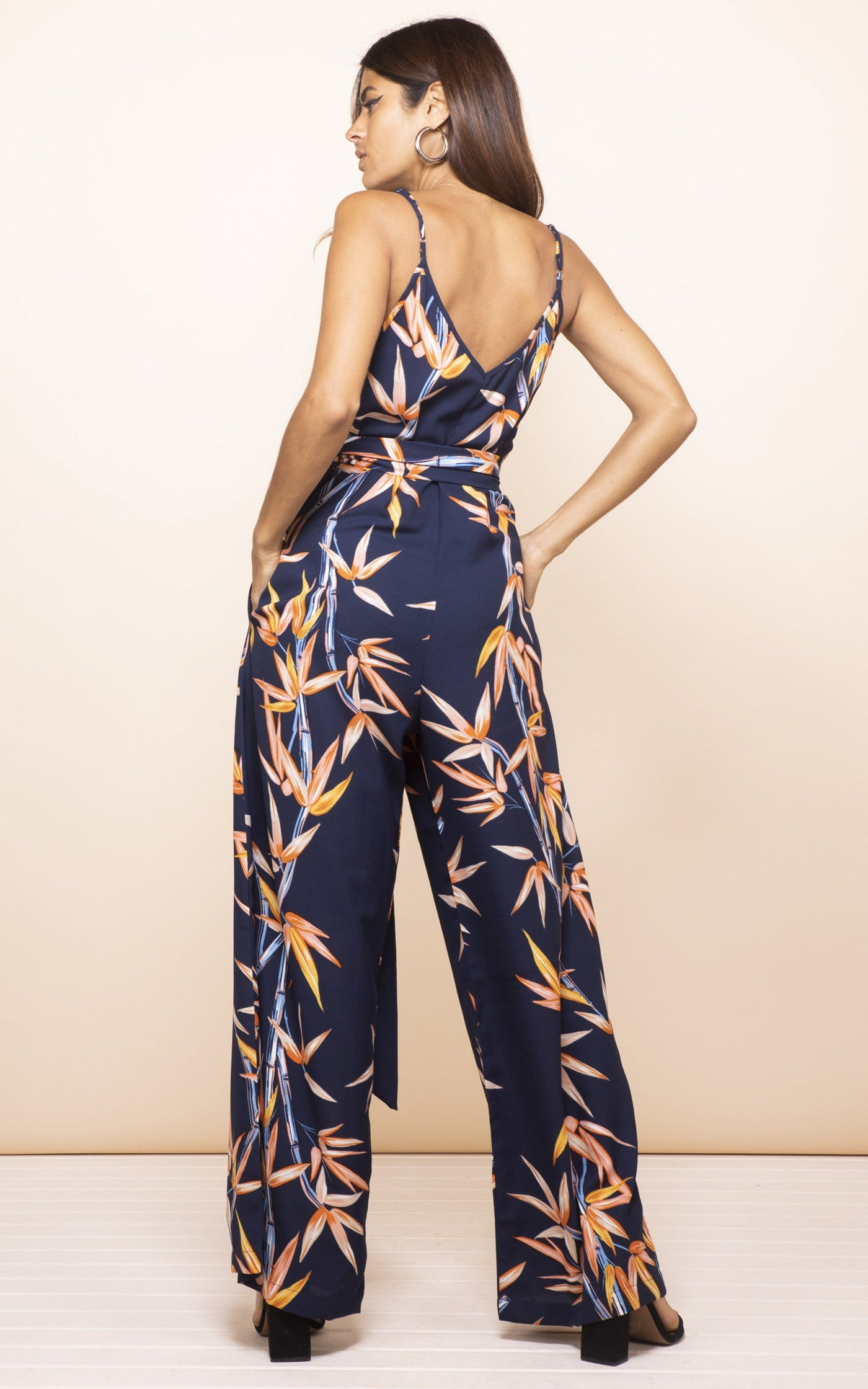 Backward-facing model with hands in pockets wears Gabriella Jumpsuit in navy bamboo print