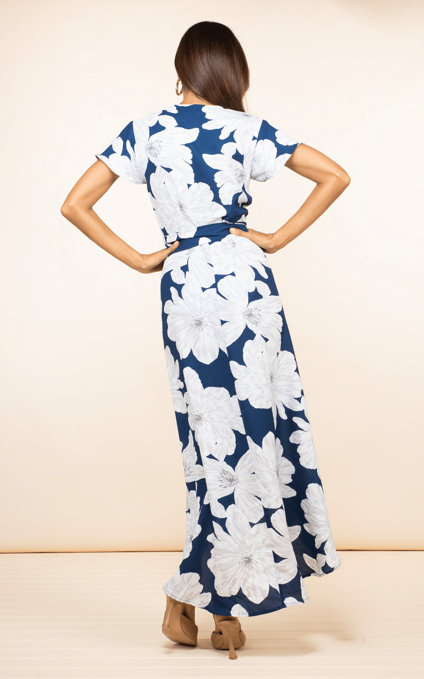 Backward-facing brunette model wears Cayenne Dress in Navy Bloom floral print by Dancing Leopard