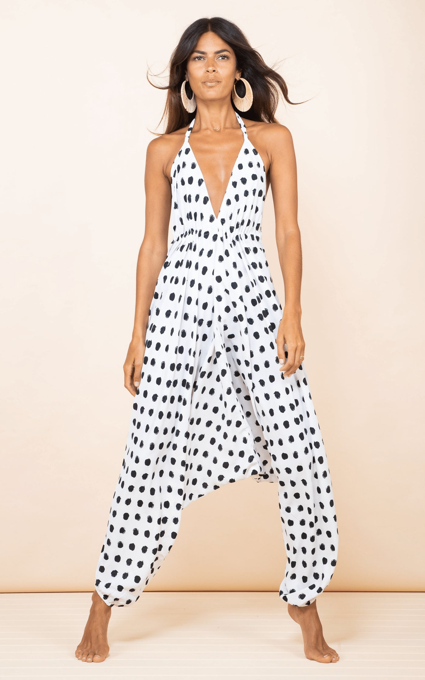 Dancing Leopard model faces forward wearing Genie Jumpsuit in white dotty print