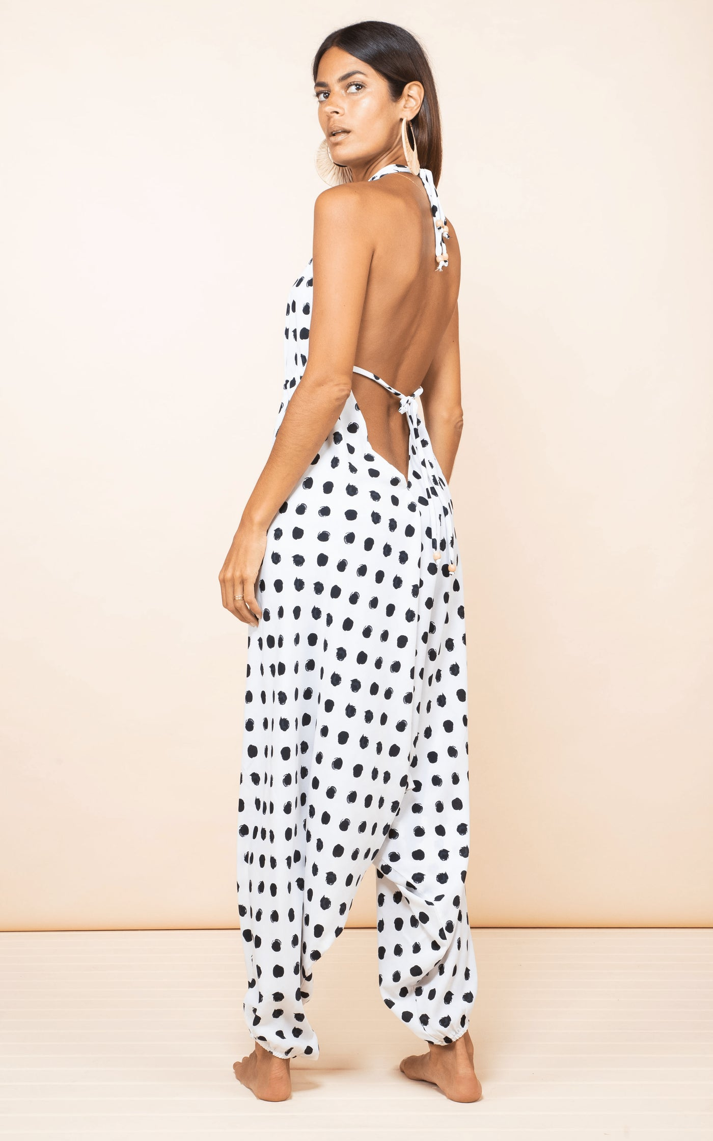 Dancing Leopard model faces sideways wearing Genie Jumpsuit in white dotty print