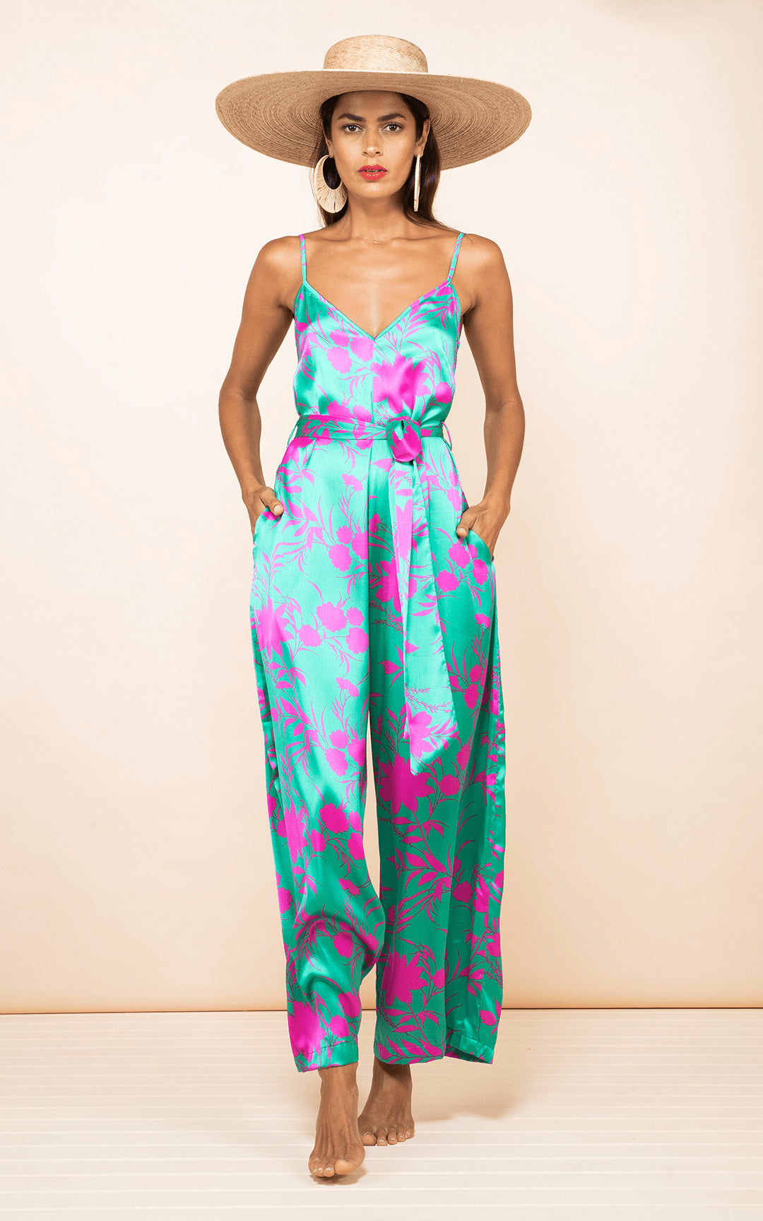 Dancing leopard model wears Gabriella Jumpsuit Silhouette Pink on Green facing forward with hands in pockets