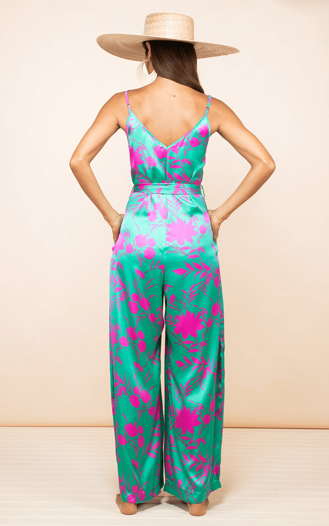 Dancing leopard model wears Gabriella Jumpsuit Silhouette Pink on Green facing the back with hands in pockets