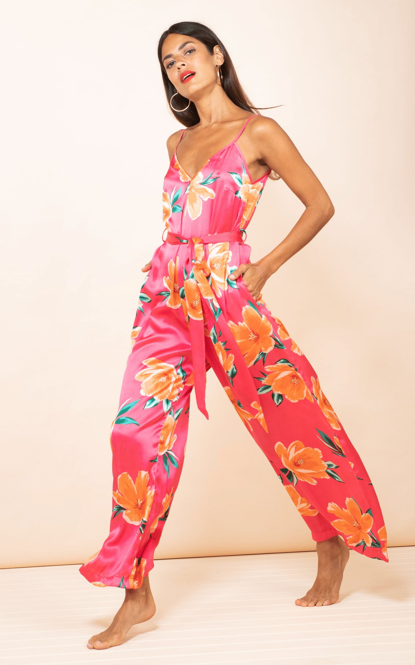 Side-facing model walks and wears Gabriella Jumpsuit in Red Base Tulip by Dancing Leopard