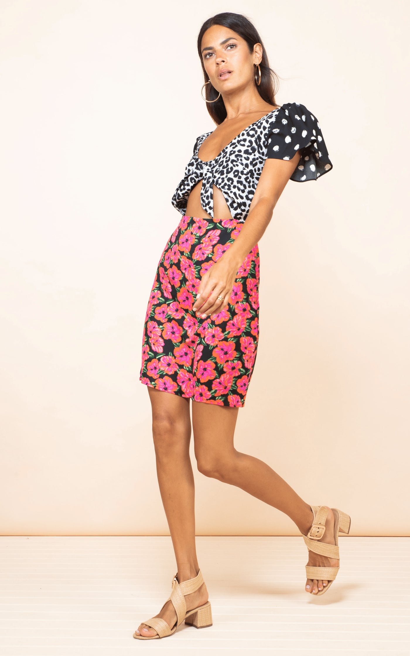 Model walks forwards wearing Dancing Leopard Mambo Mini Dress in Hibiscus Mix Print with sandals