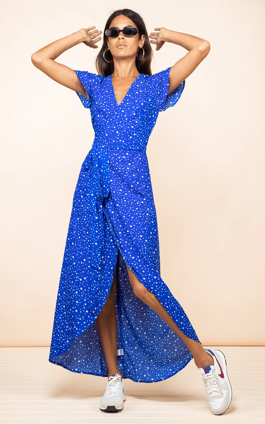 Dancing Leopard model faces forward wearing Cayenne Dress in blue star print with trainers hands up in the air