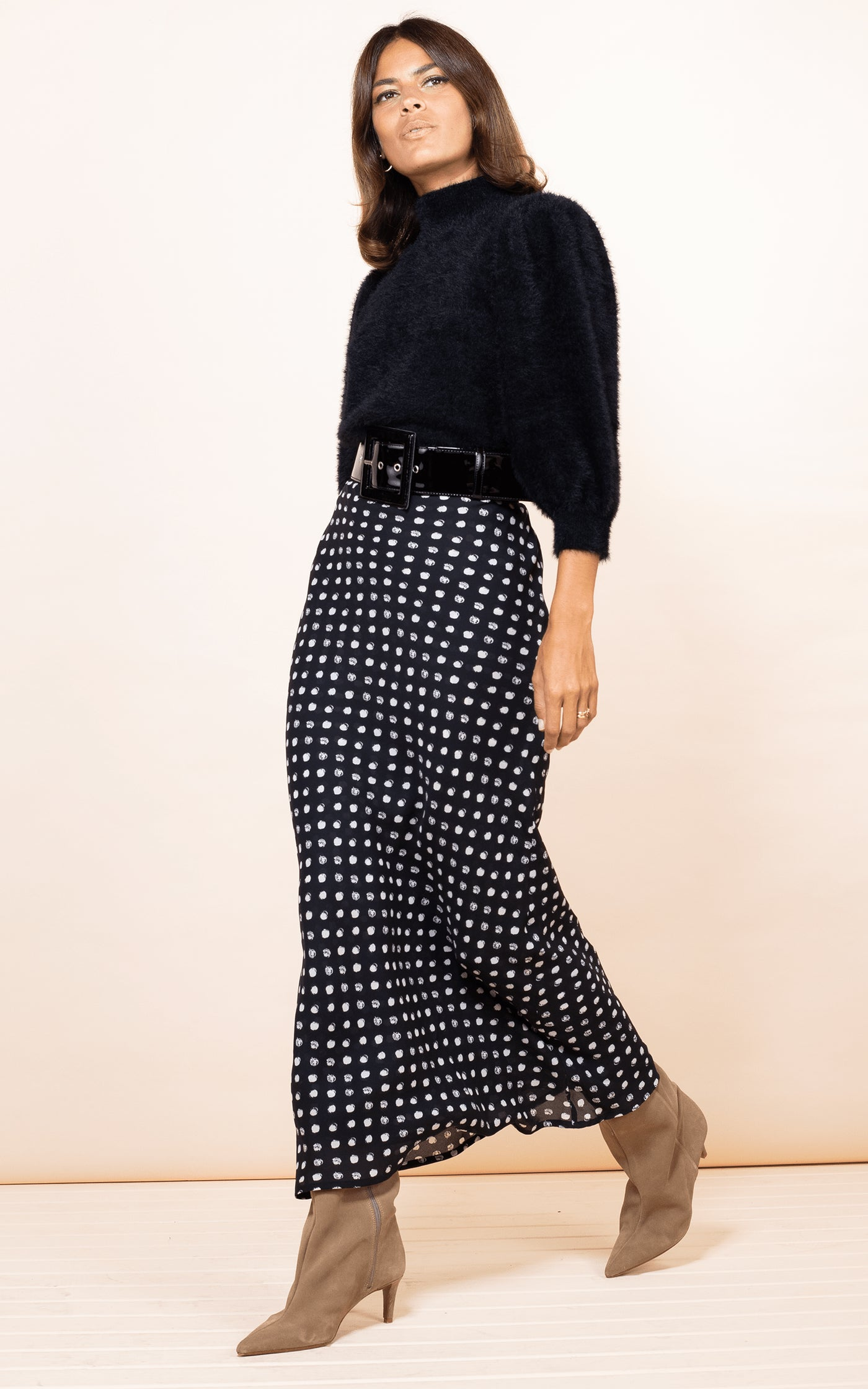 Dancing Leopard model walks forwards wearing Sophie Skirt in black dotty print with Felix Jumper