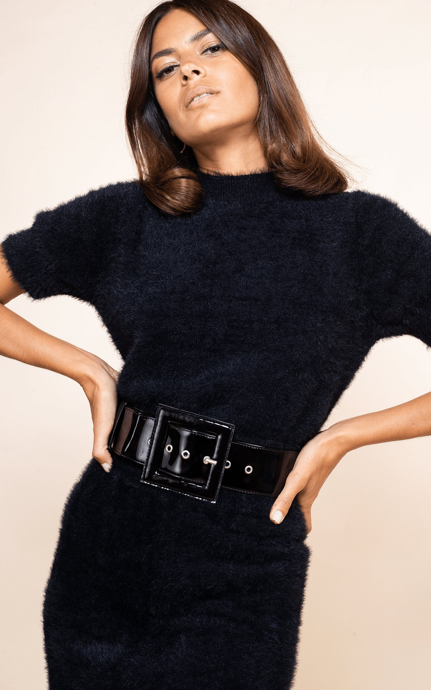 Close-up of Dancing Leopard model with hands on hips wearing Millie Knit Top in Black with belt and skirt
